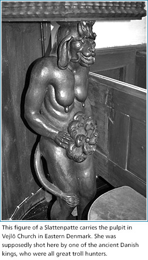 This figure of a Slattenpatte carries the pulpit in  Vejlö Church in Eastern Denmark. She was  supposedly shot here by one of the ancient Danish  kings, who were all great troll hunters.