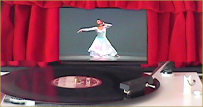 Image of a record player with video still of a woman dancing.