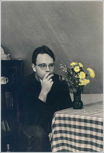 Black and white photograph of Peter Stevens (1963 - 2015) seated at a table with hand tinted yellow flowers. Photograph by Paul Lisson.